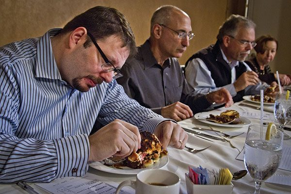 At NJM's 2011 Great Burger Showdown, Josh Ozersky, left, looked under the hood of Burger No. 1. One bite was all he needed to reach his judgment on each of the 10 entries. Photo by Marc Steiner/ANJ.
